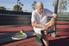 充满腿痛的资深男性网球员坐长凳在法院 免版税库存图片
