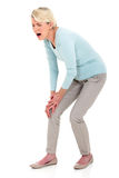 充满膝盖痛苦的妇女 免版税库存图片