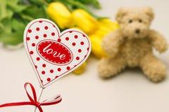 充满词爱的心脏 玩具和花在背景 免版税库存图片