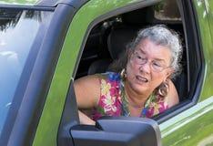 充满路愤怒的恼怒的资深妇女司机 库存照片