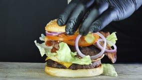 兆大汉堡用与菜和芝麻小圆面包,形成汉堡的过程的双重炸肉排,黑色的厨师 股票视频