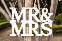 先生和White Wedding夫人在垂悬的标志上写字 免版税库存照片