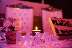 先生& Sign夫人在婚礼表上的在桃红色光 免版税库存照片