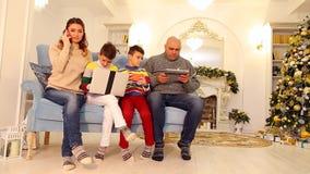 先进的家庭、两个孩子和丈夫和妻子参与他们与小配件的自己的事务娱乐的 股票视频