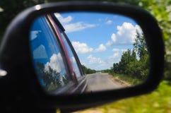 先遣旅行在农村路。汽车骑马。后视镜 免版税库存照片
