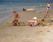 先驱,俄罗斯 在沙子的儿童游戏在波罗的海 晴朗蓝色日房子加里宁格勒地区屋顶俄国的夏天 库存图片