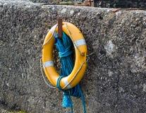 光亮救生圆环和浮力在港口墙壁上垂悬在爱尔兰的北海岸的Ballintoy 免版税库存图片