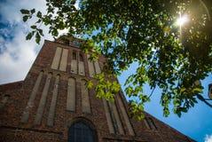 光亮的太阳配齐在古老教会前面的一棵树 库存照片