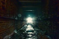 光和出口在黑暗的长的砖的末端放弃了工业隧道或走廊或者下水道渠道,方式对自由概念 库存照片