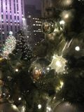 光和球装饰品在一棵圣诞树与雨下落在雨以后在晚上 免版税库存图片