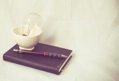 光和铅笔在笔记本葡萄酒 免版税库存图片