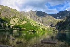 光和阴影从明亮的多云天空在湖 免版税图库摄影