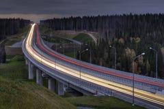 光在四车道的高速公路落后,穿过夜森林 免版税库存照片