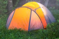 光在帐篷,一个早期的有雾的夏天早晨烧 免版税库存照片