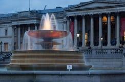 光在特拉法加广场,威斯敏斯特,伦敦,黄昏的英国在其中一个照亮水喷泉中 免版税库存照片