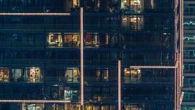光在现代多个故事大厦窗口里在城市布局的在夜timelapse 股票录像