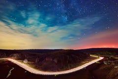 光在路和美丽的满天星斗的天空落后在多布罗加小山  免版税库存照片
