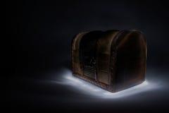 光在黑背景的被绘的木胸口 免版税库存照片