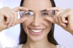 光学和玻璃,看thro的年轻微笑的妇女画象  库存图片
