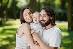 光彩的母亲、残酷在白色衣裳打扮的父亲和他们迷人的小女儿温暖地拥抱  免版税库存图片
