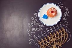 光明节与menorah的假日在黑板的背景和sufganiyot 在视图之上 免版税库存照片
