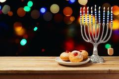 光明节与menorah的假日sufganiyot在木桌上