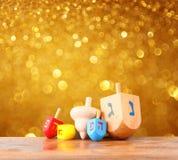 光明节和闪烁金黄光背景的木dreidels 免版税库存照片