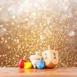 光明节和闪烁金黄光背景的木dreidels 免版税库存图片