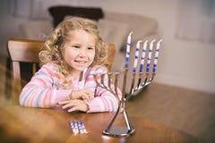 光明节:坐在表上的女孩准备好点燃蜡烛 库存图片