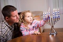 光明节:女孩和父母光一起光明节蜡烛 库存图片