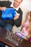 光明节:父亲打开光明节礼物 图库摄影