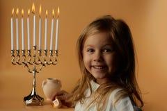 光明节:蜡烛光明节背景的女孩  免版税图库摄影