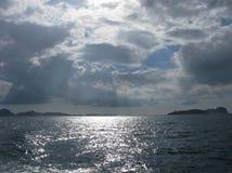 光束通过在海的黑暗的云彩 免版税库存图片