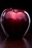 光泽在黑暗的背景的红色苹果计算机 库存图片