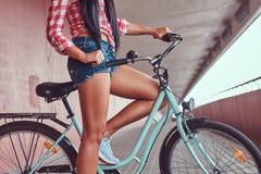 光滑的亭亭玉立的女性腿的特写镜头图象在蓝色运动鞋的在城市自行车附近 库存照片