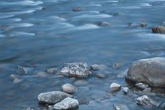 光滑的水表面的长的曝光照片在小山的 免版税库存图片