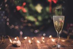 光滑的遮荫圣诞节和新年与圆的bokeh的装饰背景、金黄丝带和香槟和黄柏 免版税库存图片