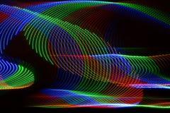 光漩涡以蓝绿色和红色有黑背景 图库摄影