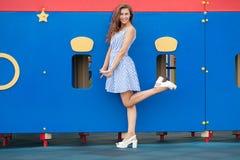 光的年轻深色的妇女镶边了白色蓝色礼服获得乐趣在室外的操场 图库摄影