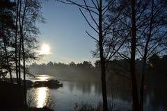 光秃的被停泊的冬天树和小船 免版税库存图片