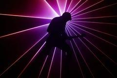 光背景的吉他弹奏者  免版税库存照片