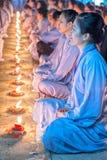 光芒四射的在每个蜡烛里面的秀丽面部女性佛教徒 免版税库存图片