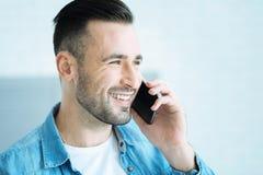 光芒四射的年轻人谈话在电话和微笑 库存照片