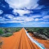 光蓝色条纹在土路的反对多云天空 免版税库存图片
