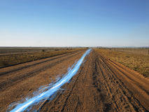 光蓝色条纹在土路的反对清楚的天空 库存图片