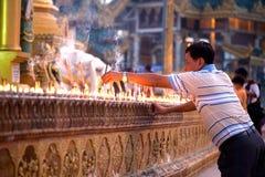 仰光,缅甸- 1月29 :一个佛教徒人点燃偶象stickat Shwedagon寺庙2010年1月29日 免版税库存照片