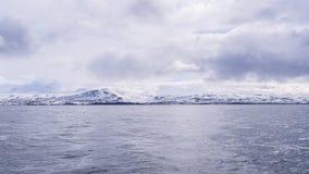 光滑发光的水和史诗多雪的山 免版税库存图片