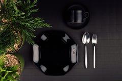 黑光滑的板材,匙子,叉子,毗邻绿色植物作为典雅的minimalistic菜单的,顶视图eco友好的大模型 免版税库存图片