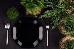 黑光滑的板材,匙子,叉子,毗邻绿色植物当eco友好的嘲笑为菜单餐馆,顶视图 免版税库存图片