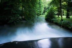 光滑的河在有剧烈的光的森林 免版税库存照片